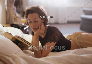 Woman In Bed Alone Reading Book Stock Photo