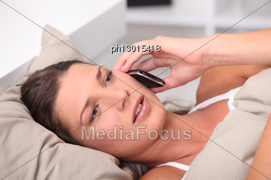 Woman In Bed Telephoning Stock Photo