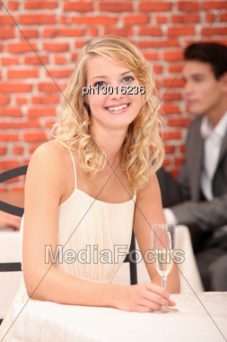 Woman In Restaurant With A Glass Of Champagne Stock Photo