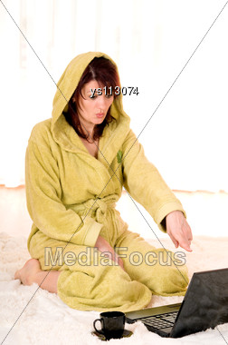 Woman In Robe With Laptop Sitting On The Floor Stock Photo