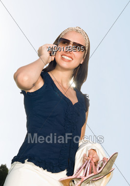 Woman In Sunglasses Talking On Cellular Stock Photo