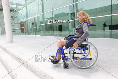 Woman In A Wheelchair Outside An Office Building Stock Photo