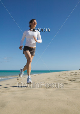 Woman Jogging On The Beach Stock Photo