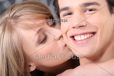 Woman Kissing Her Boyfriend Stock Photo