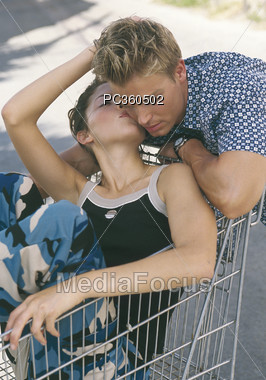 Woman Kissing Man On The Neck Stock Photo