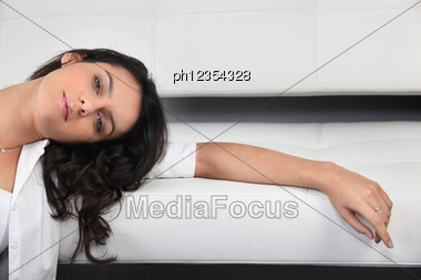 Woman Leaning Her Arm On Sofa Stock Photo
