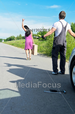 Woman Is Leaving Mechanic Alone Near The Broken Car. Stock Photo
