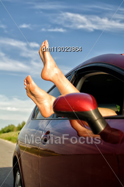 Woman's Legs Out Of The Car Window. Concept Of Carefree Funny Trip. Stock Photo