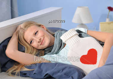 Woman Lies In Bed With Hot Water Bottle Stock Photo
