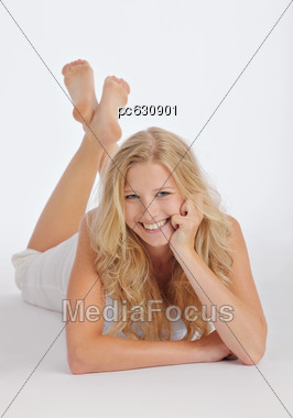 Woman Lies Relaxed On The Floor, Smiles Stock Photo