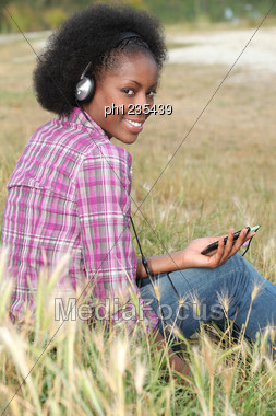 Woman Listening To Music In A Field Stock Photo