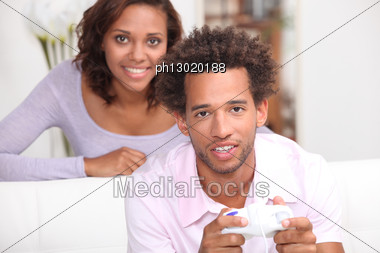 Woman Looking At Her Boyfriend Playing Video Games Stock Photo