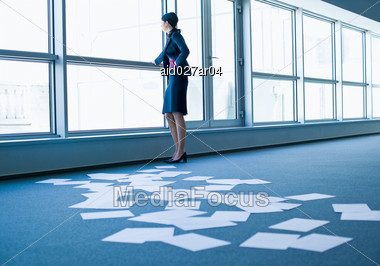 Woman Looks Out Of Window, Papers Lying On The Ground Stock Photo