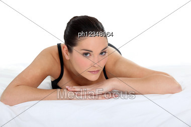 Woman Lying On A Bed In Her Underwear Stock Photo