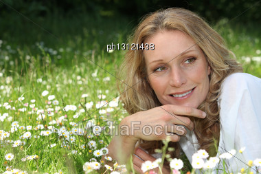 Woman Lying In A Meadow Stock Photo