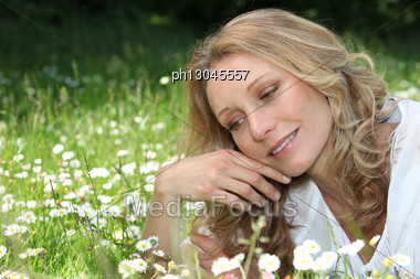 Woman Lying In Daisies Stock Photo