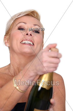 Woman Opening Bottle Of Champagne Stock Photo