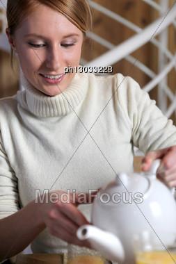 Woman Pouring Tea Stock Photo