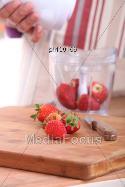 Woman Putting Strawberries In A Blender Stock Photo