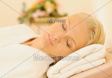 Woman Resting Head On Towels In Spa Stock Photo