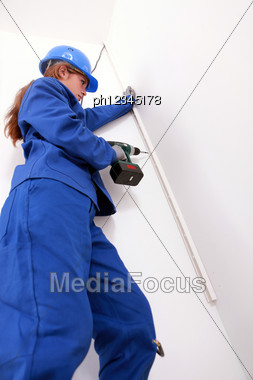 Woman Screwing A Molding Stock Photo