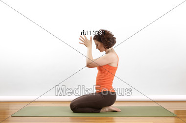 Woman Showing A Anjili Mudra Yoga Pose On A Green Mat Stock Photo