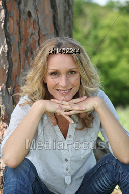 Woman Sitting By Tree Stock Photo