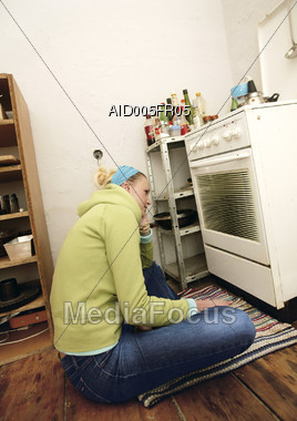 Woman Sitting On Floor Waiting For Oven Stock Photo
