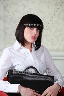 Woman Sitting In A Chair With A Briefcase Stock Photo