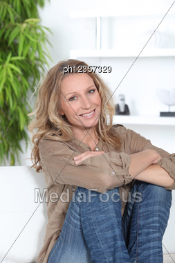 Woman Sitting On A Couch Stock Photo