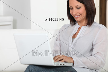 Woman Sitting On Couch With Computer Stock Photo