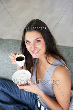 Woman Sitting On A Sofa With A Cup Of Coffee Stock Photo