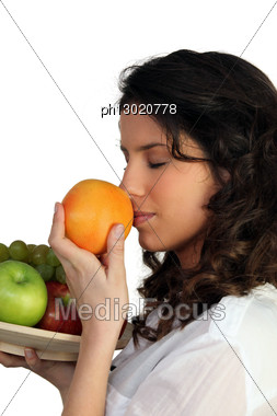 Woman Sniffing Orange Stock Photo