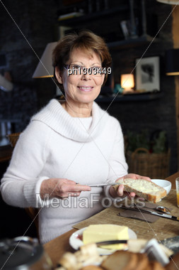 Woman Spreading Butter On A Piece Of Bread Stock Photo
