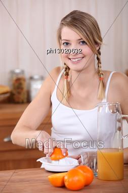 Woman Squeezing Oranges. Stock Photo