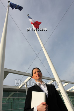 Woman Standing Next To French And European Flagpoles Stock Photo