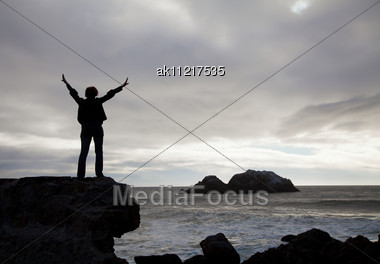 Woman Staying With Raised Hands Against Sunset At The Ocean Stock Photo