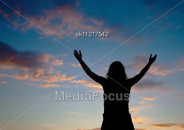 Woman Staying With Raised Hands At The Sunset Time Stock Photo