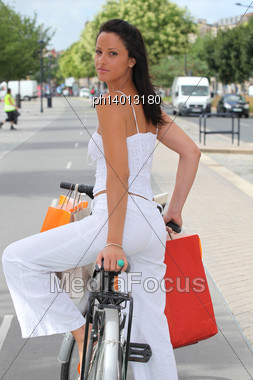 Woman With Store Bags Riding A Bike In The City Stock Photo