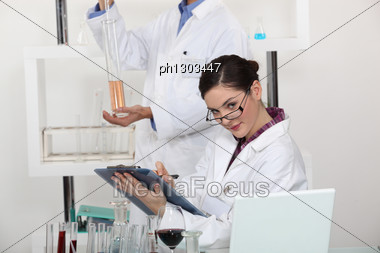 Woman Taking Notes In Her Lab. Stock Photo