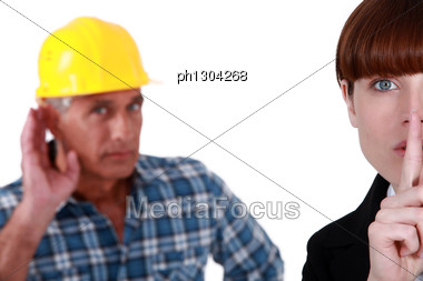 Woman Telling Builder To Be Quiet Stock Photo