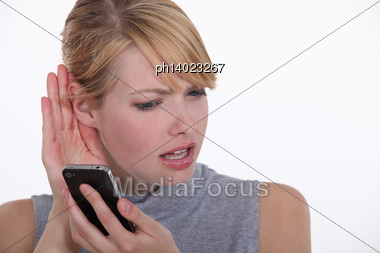 Woman Trying To Hear A Person On Her Cell Phone Stock Photo