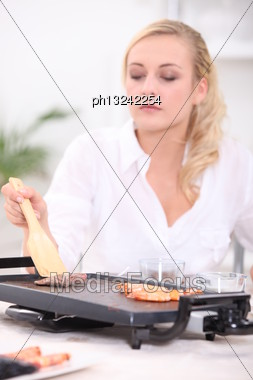 Woman Using Griddle Stock Photo