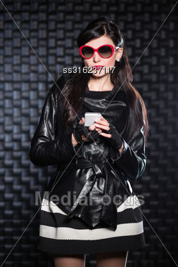 Woman Wearing Black Jacket And Red Sunglasses Posing With A Mobile Phone Stock Photo