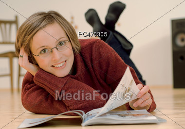Woman Wearing Glasses Reading On Floor Stock Photo