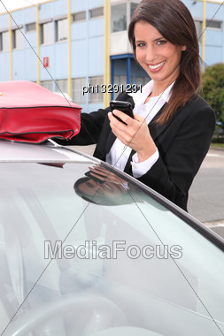 Woman With A Phone By Her Car Stock Photo