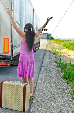 Woman With Suitcase Hitchhiking A Car Stock Photo