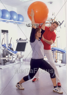 Women Exercising With Swiss Ball & Personal Trainer Stock Photo