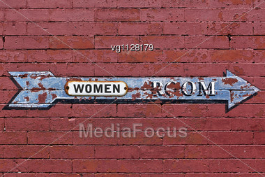 Women Room Arrow Directional Weathered Sign Over Red Brick Wall Stock Photo