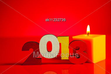 Wooden 2013 Year Number With A Burning Candle Over Red Background Stock Photo